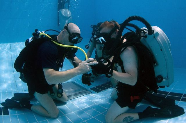 The US navy drivers check the pressure gauge during a training dive.